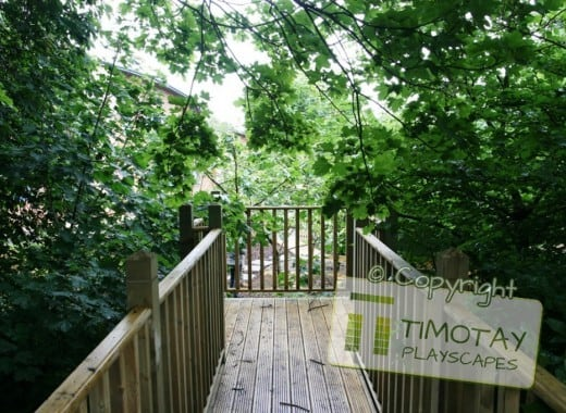 Wooden walkway in forest with Timotay Playscapes logo overlaid
