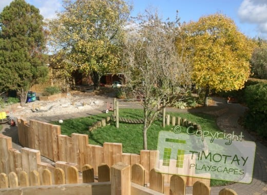 Wooden fences overlooking greenery with Timotay Playscapes logo overlaid