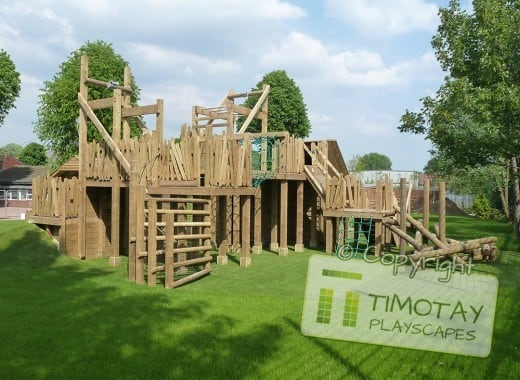 Woodjungle gym in forest with Timotay Playscapes logo overlaid